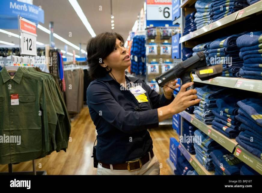 A female associate uses a Telxon handheld scanner to read ...