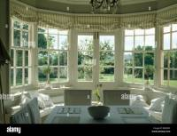 Striped blinds on French windows in dining room with view ...
