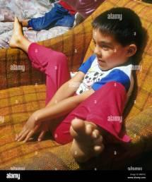 Young Hispanic Boy Pajamas Sits Funny Feet Chair Fun