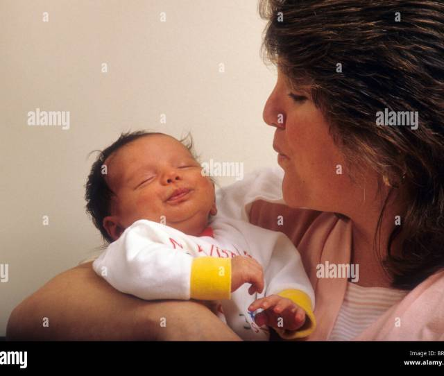 White Mom Mother Blows Kiss Onto Baby Infant Newborn Smile Love Hold Cuddle Son Smile Happy Cozy