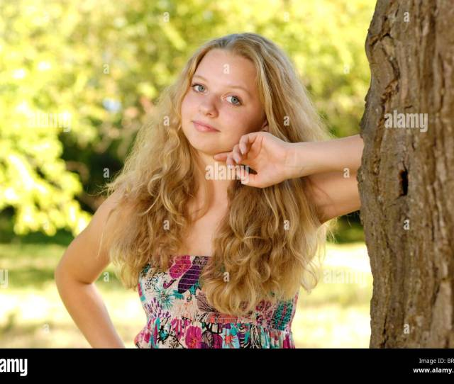 Happy Attractive Long Haired Blond Teenager Girl Near The Tree
