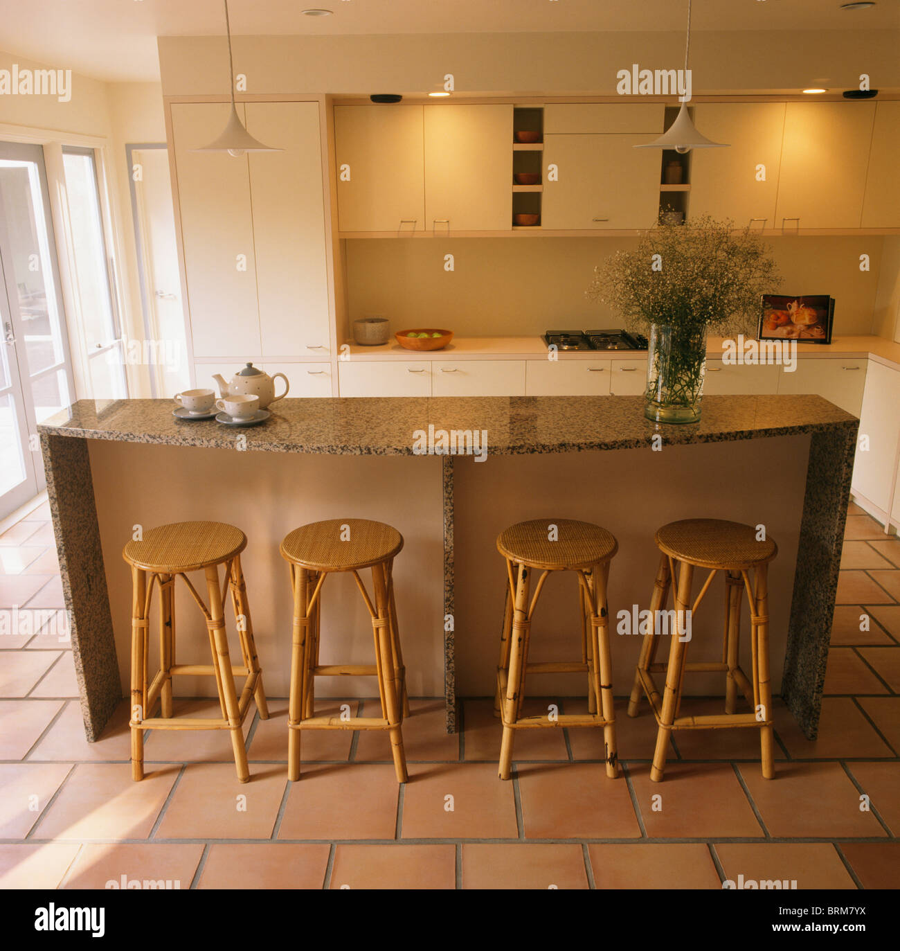 modern kitchen stools curtain rods cane at breakfast bar on granite topped island unit in with down lighting above cupboards