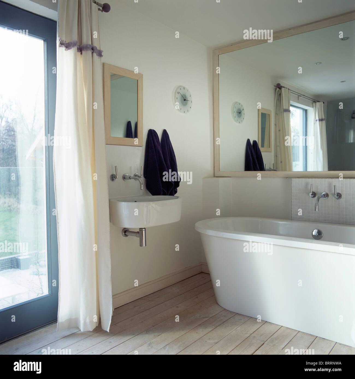 Large mirror above modern bath in small modern bathroom