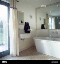 Large mirror above modern bath in small modern bathroom