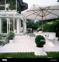 Large white umbrella above white chairs and table on white ...