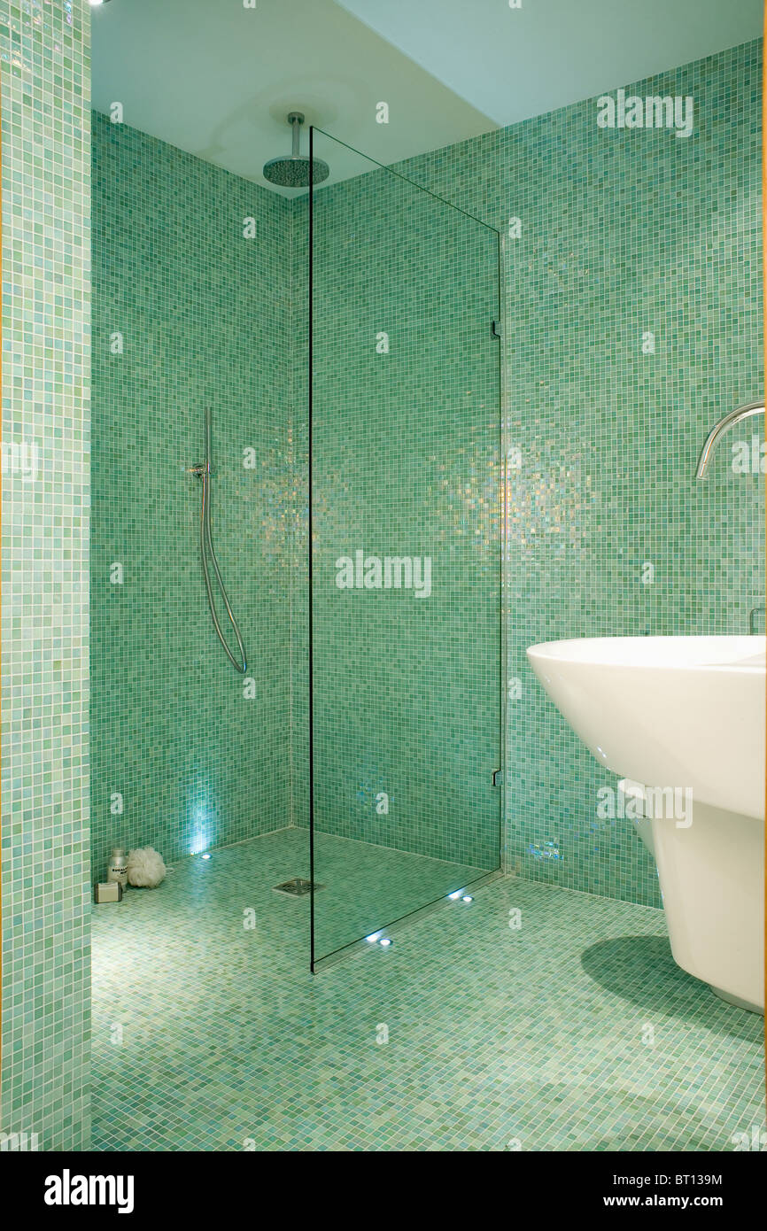 Glass screen on walkin wetroom shower in modern green mosaic tiled Stock Photo Royalty Free