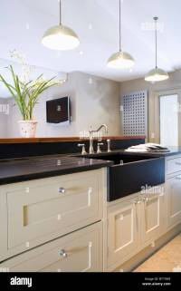 White pendant lights above black sink in cream fitted