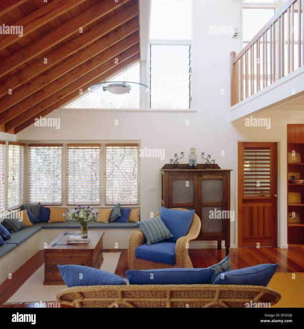 Built-in seating with blue cushions below windows in ...