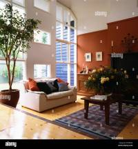 White sofa and tree in pot in large modern split-level ...