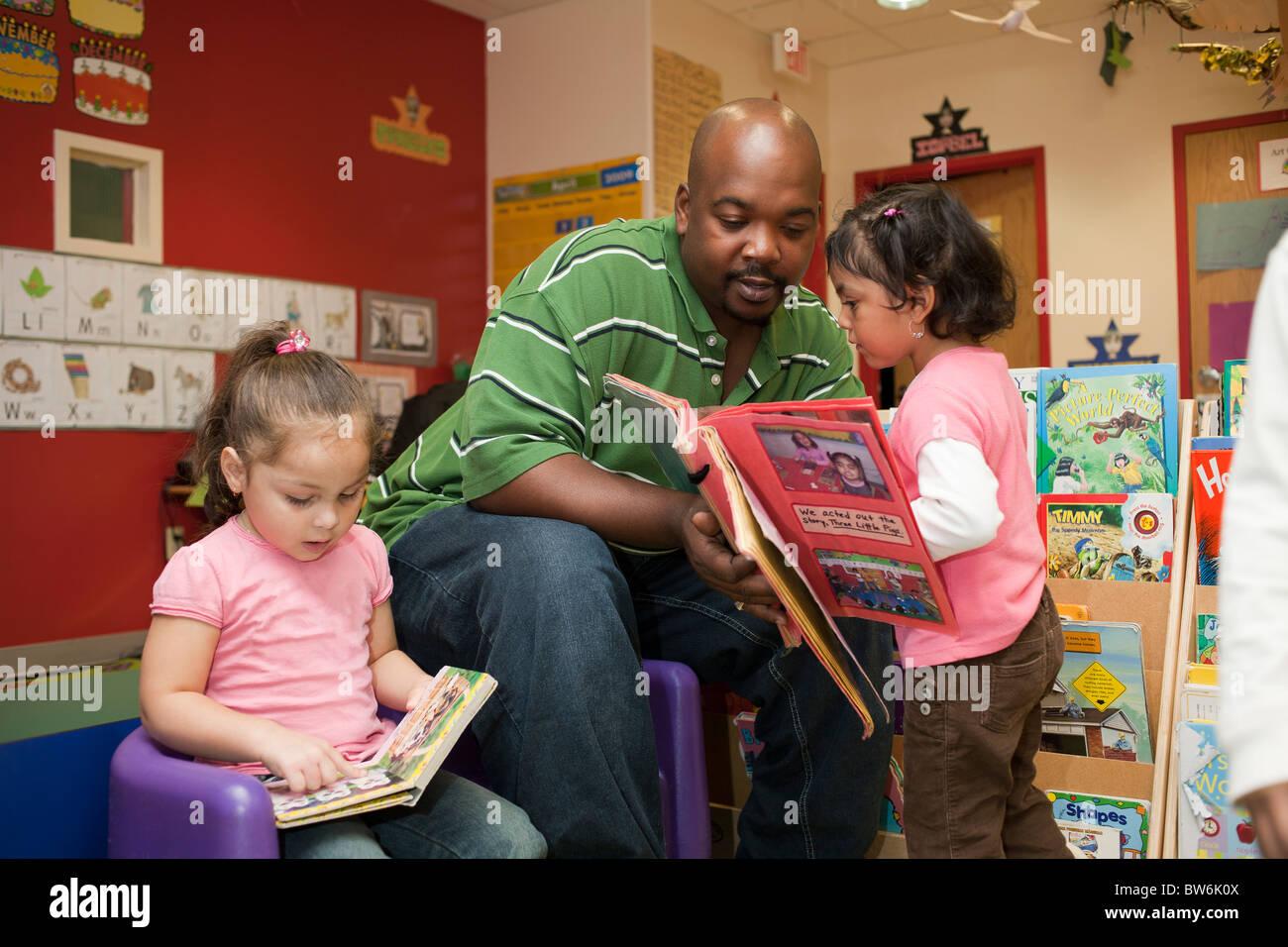 Male African American Preschool Teacher Helping A Girl