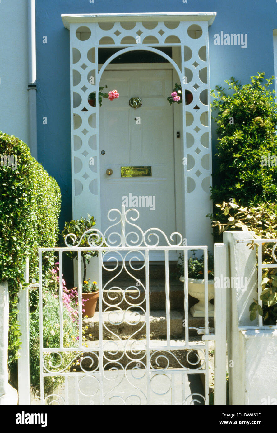 White Wrought Iron Gate In Front Of Small House With White