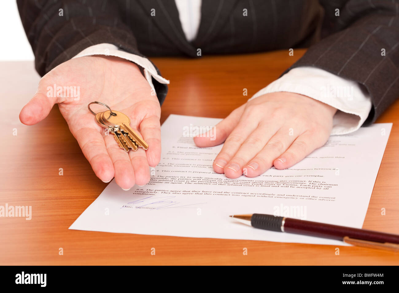 Business Woman Holds Key And Contract In Hands. Isolated On White  Background. - Stock