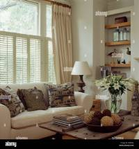 Cream curtains and plantation shutters on window above ...