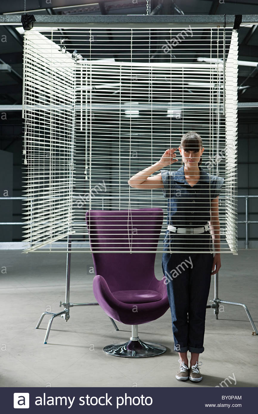 Young Woman And Purple Swivel Chair Behind Venetian Blind