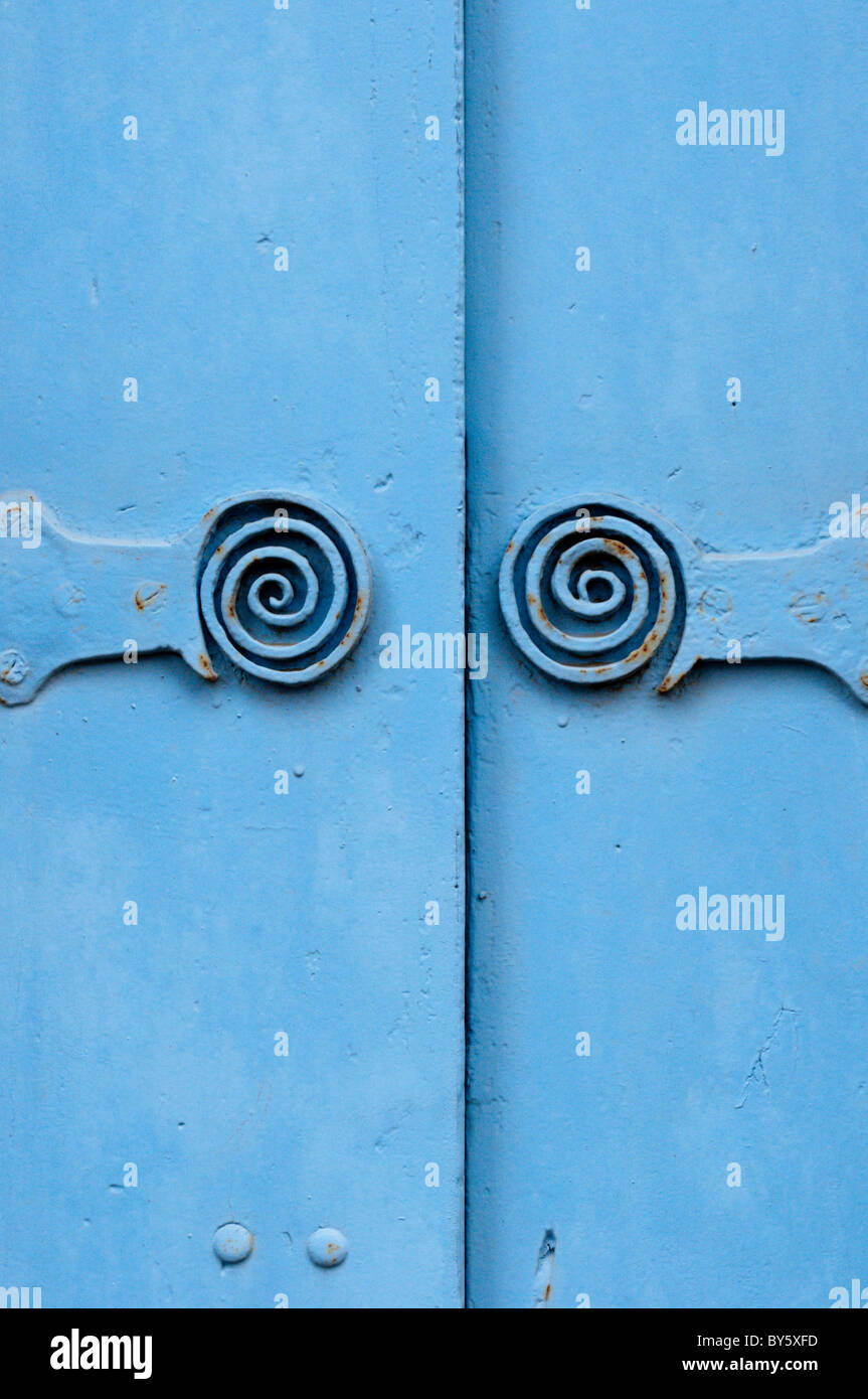 Symmetrical Metal Hinges With A Decorative Spiral On Blue