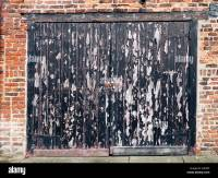 Old wooden garage door in need of redecoration with black ...