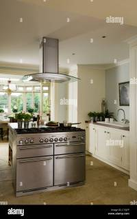 Modern white kitchen with stainless steel island hob and ...