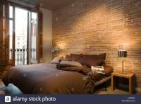 modern brown bedroom with bare brick wall and full-length ...