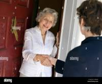 Smiling senior woman greeting visitor at the front door ...