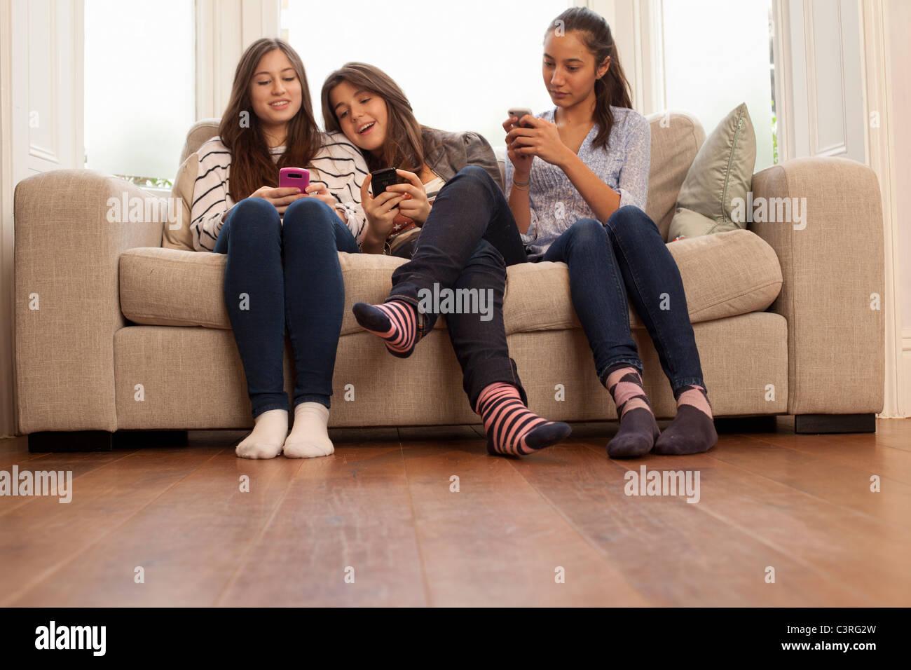teenage girls sitting on sofa looking at phones Stock Photo 36782225  Alamy
