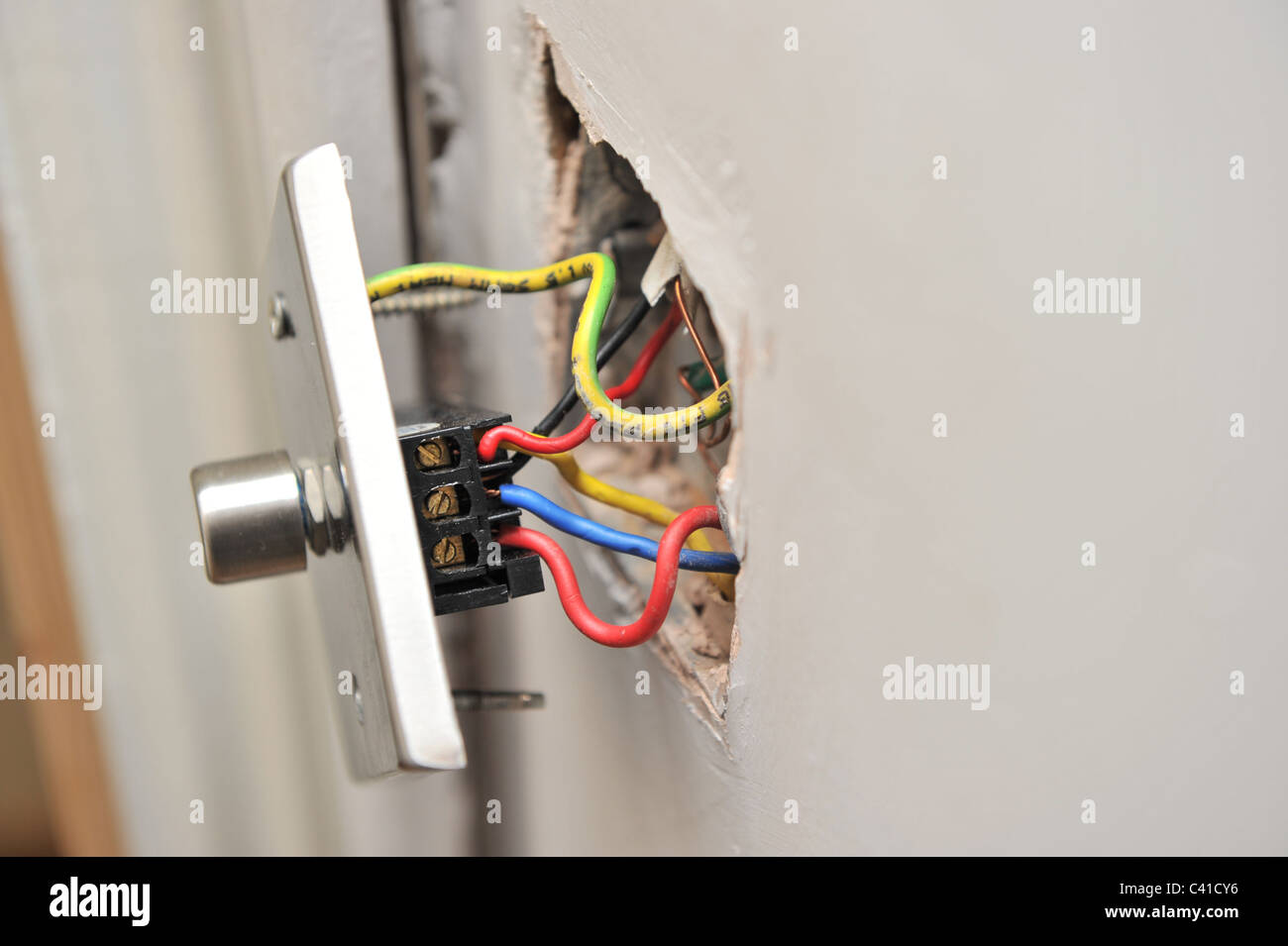 hight resolution of a faulty house light dimmer switch pulled away from wall showing electrical wires in parallel during diy