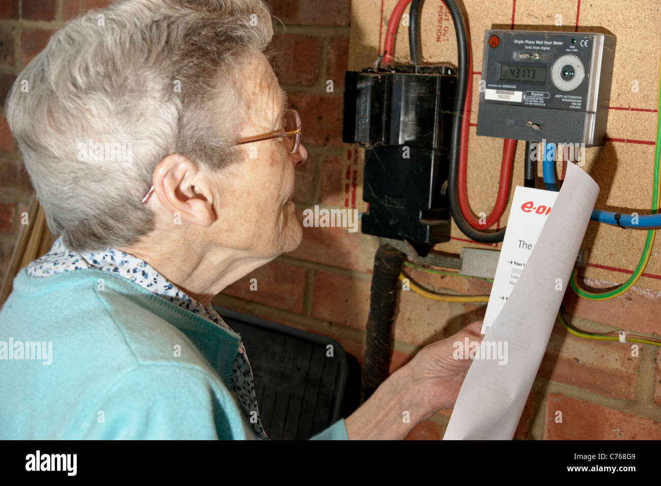 hight resolution of elderly woman looking checking electricity and gas utility bills with the meter in case of discrepancies
