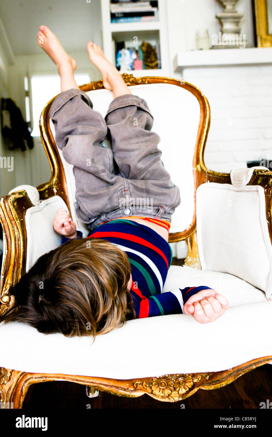 Little boy sitting upside down on chair Stock Photo