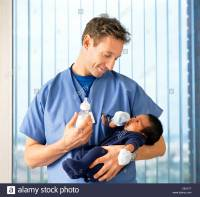 Doctor with baby bottle holding newborn baby boy in ...