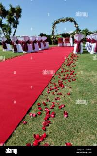Outdoor wedding setting with red carpet flower petals ...