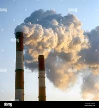 Air pollution by smoke coming out of two factory chimneys ...