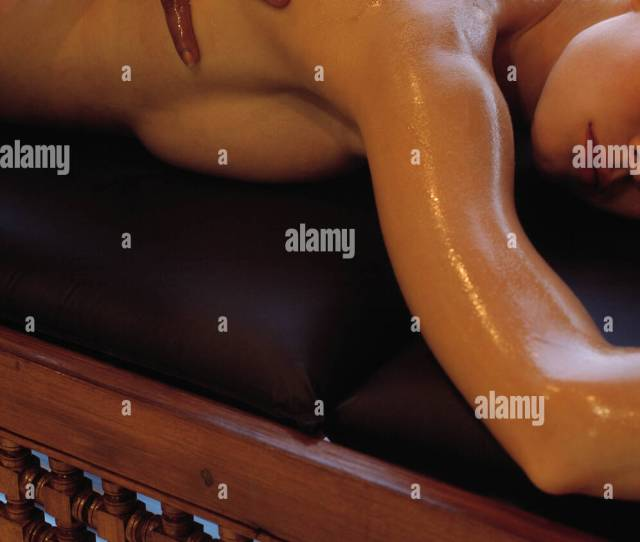 Cropped Image Of Female Lying On Front On Black And Wooden Bed Having Back Massage Arms Above Head Body Glistening Massage Oil