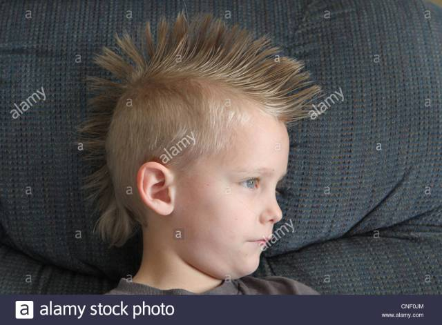 a close up of a little boy with a blond mohawk stock photo