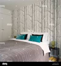 Blue cushions on double bed against wall with tree pattern ...