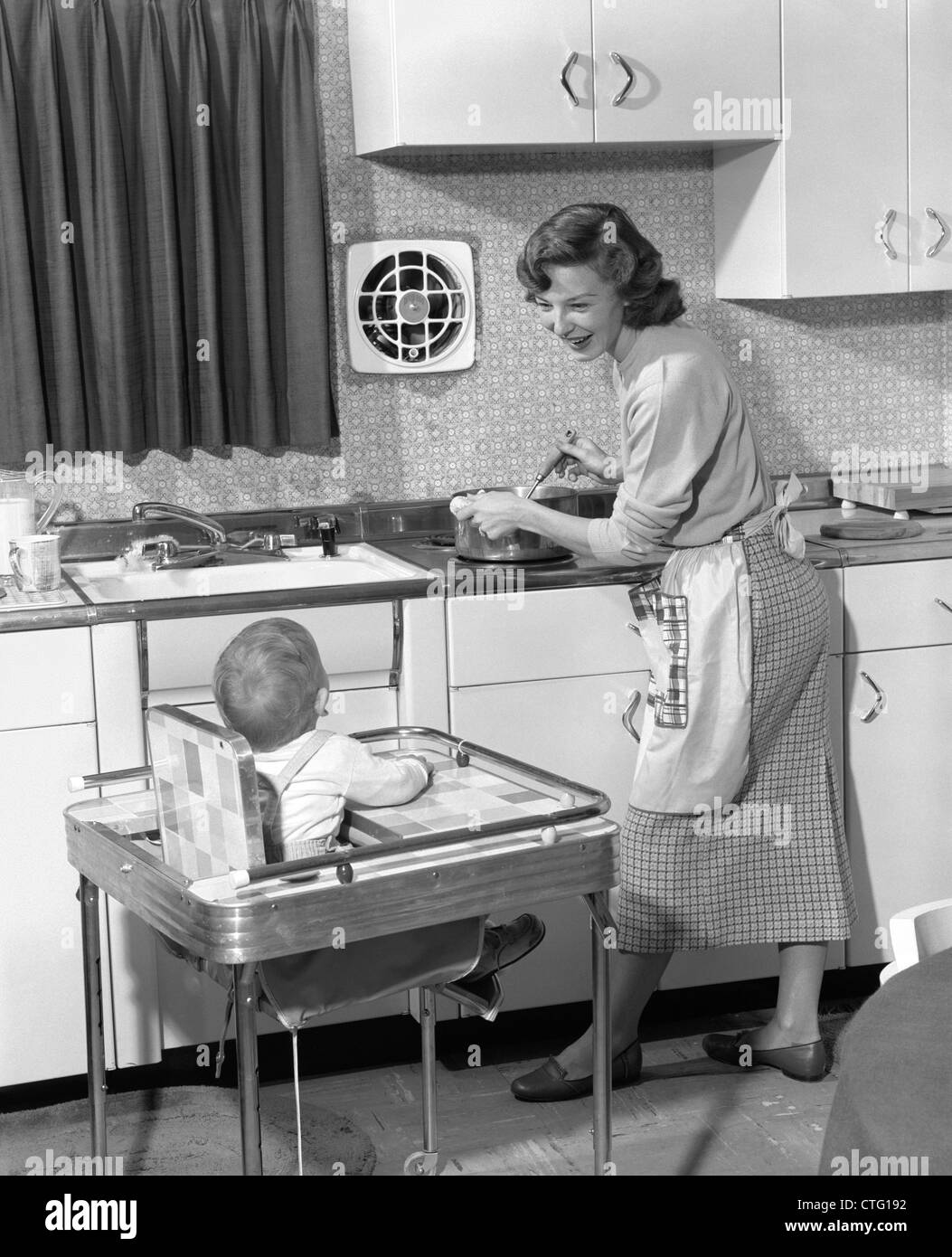 retro high chairs babies joovy portable chair 1950s woman mother in home kitchen cooking pot on stove smiling at baby child