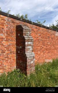 Old rustic red brick garden wall with buttress, Derbyshire ...
