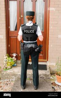 Police woman waits at the front door of a house Stock ...