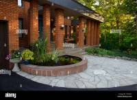 Front entrance with pond and stone veranda on red brick ...