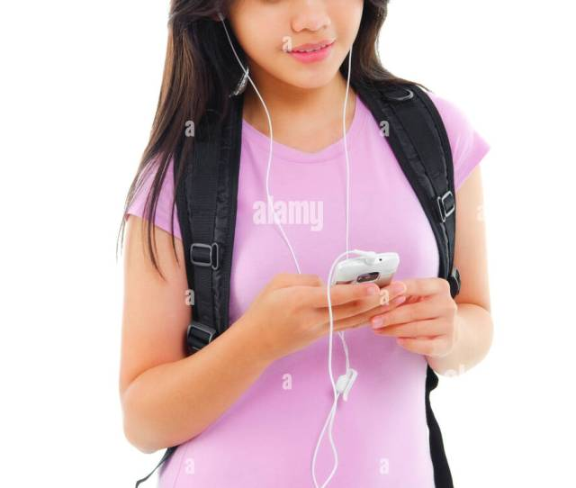 Young Asian Teen Texting And Listening To Music