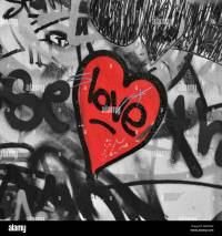 Red painted love heart on graffiti covered black and white ...