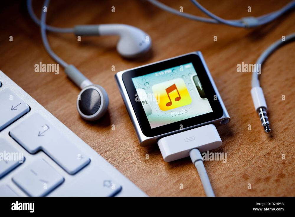 medium resolution of ipod nano with a cable attached sits on a desk next to apple earbud headphones and a computer keyboard