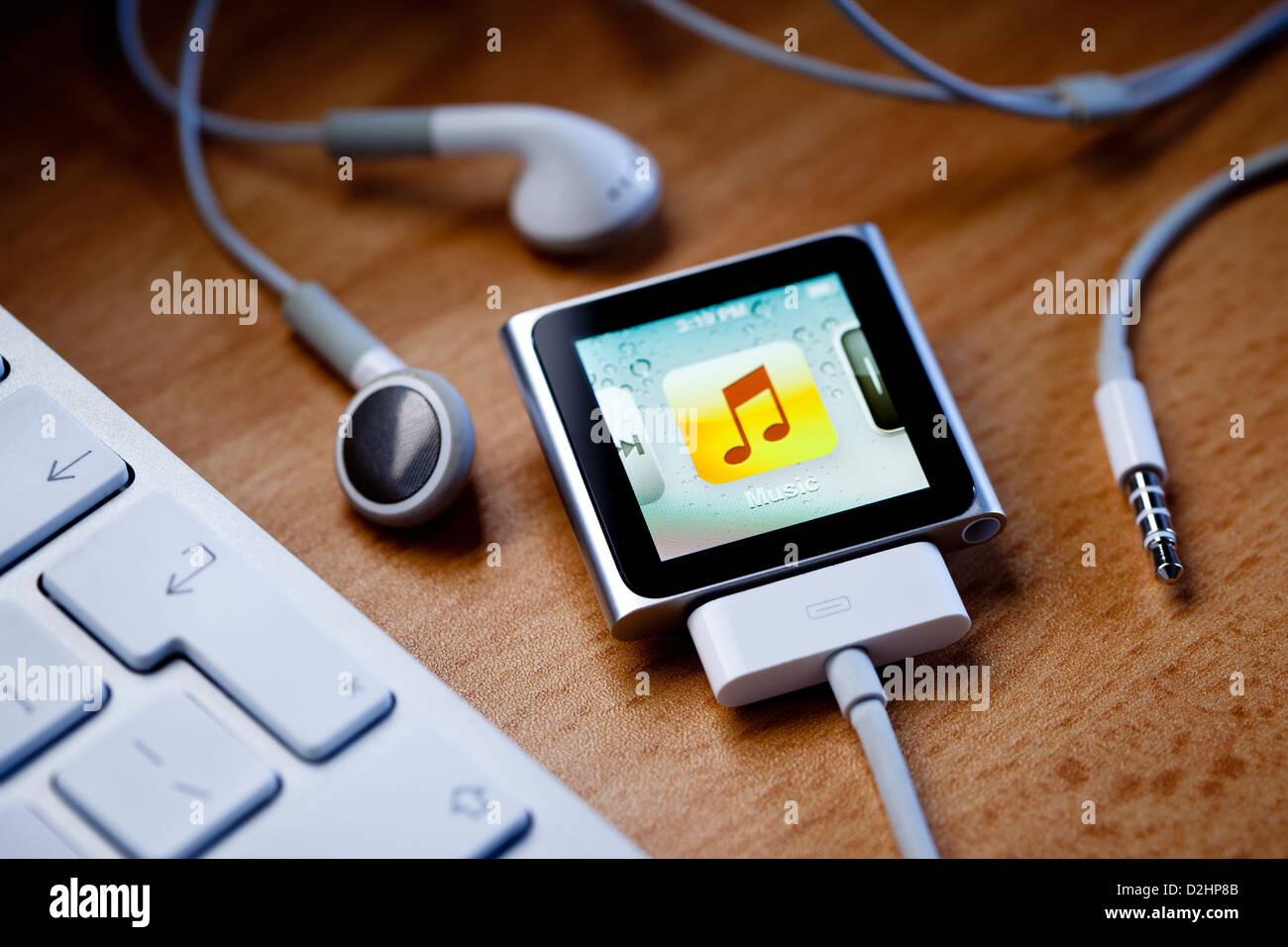 hight resolution of ipod nano with a cable attached sits on a desk next to apple earbud headphones and a computer keyboard