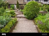 Gravel pathway through kitchen garden borders leading to ...
