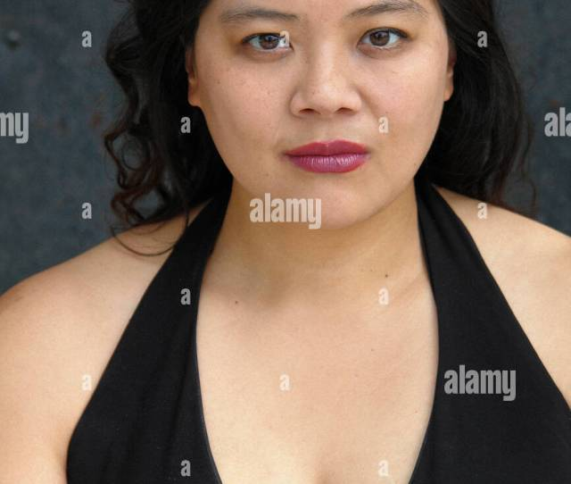 Head And Shoulders Portrait Of Heavy Set Asian American Woman Of Chinese Ethnicity With Long Black Hair Wearing A Black Halter