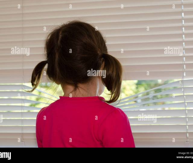 Depressed Lonely And Abused Little Girl Looks Outside Through Window