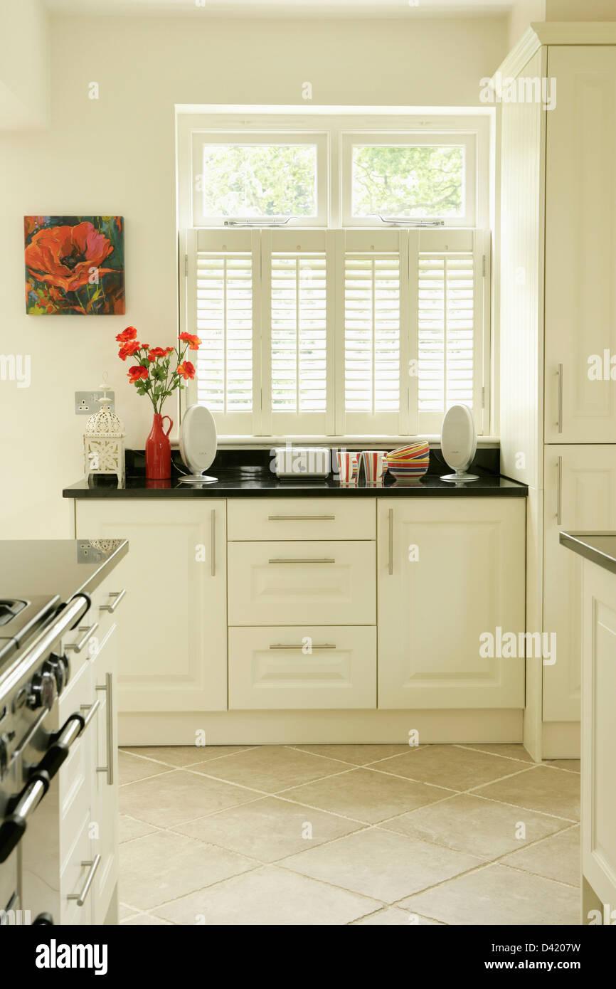 White Plantation Shutters On Window In Modern White Kitchen