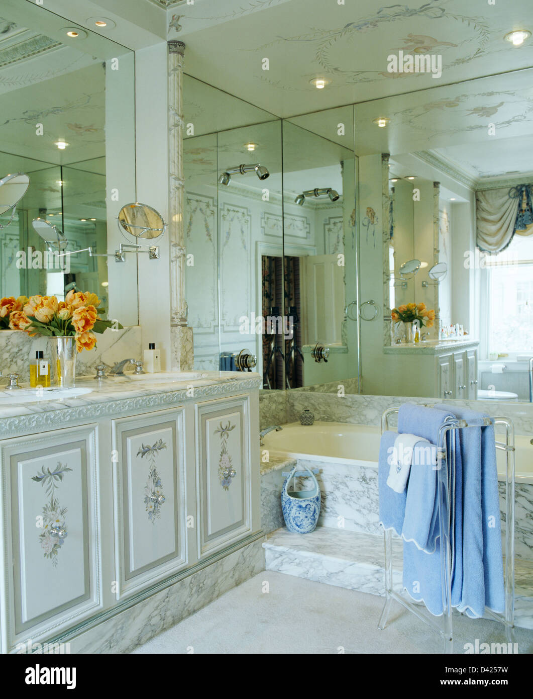 Mirrored walls and marble paneled bath in townhouse