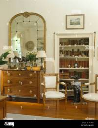 Large antique mirror above chest of drawers in country ...