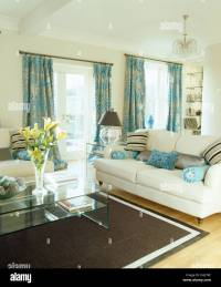 Patterned turquoise curtains and cream sofas in cream ...