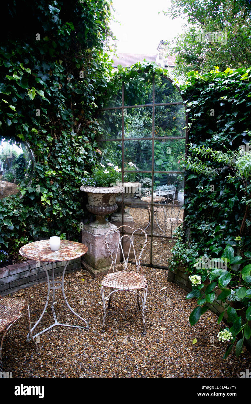 old metal chairs chair cushions outdoor target table and on gravel in front of arched window shaped mirror townhouse garden with ivy covered walls
