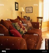 Patterned cushions on rust colored sofa in traditional ...